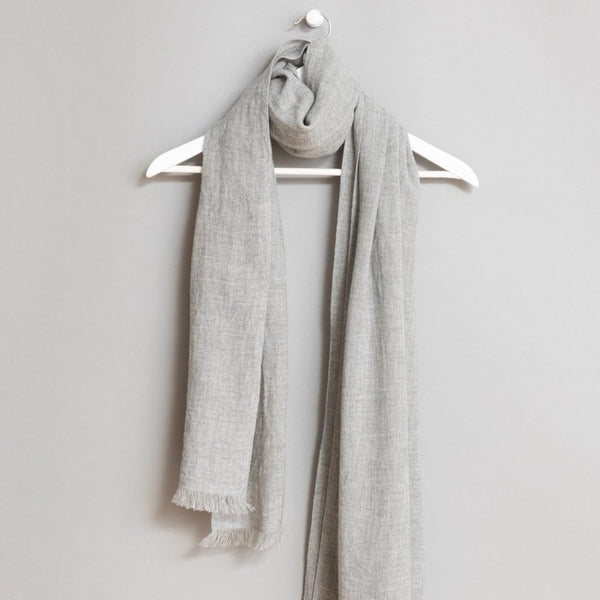 Grey scarf wrapped around a white wooden hanger. The scarf has frayed edges. The Merino Woven Scarf in Flint Grey is from designer Dinadi.
