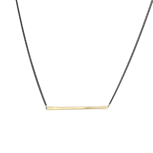 betsy & iya necklace with gold brass bar and black chain.