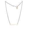 betsy & iya Divisionary necklace with gold brass bar and black chain.