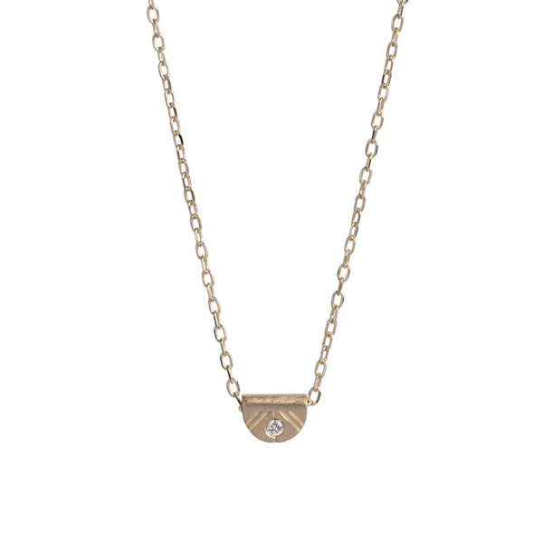 Tiny, half-moon pendant of 14k yellow gold, inlaid with a white diamond, and affixed to a delicate gold chain. Hand-crafted in Portland, Oregon.