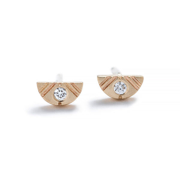 Tiny, half-moon stud earrings of 14k yellow gold with round, white diamond inlays, and 14k gold earring posts. Hand-crafted in Portland, Oregon.