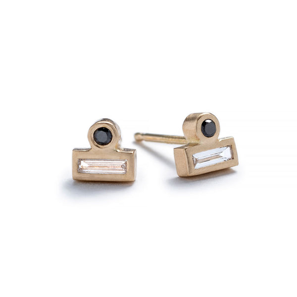 Tiny stud earrings of 14k yellow gold, featuring a small, round, black diamond set against the long side of a white diamond baguette. Hand-crafted in Portland, Oregon.