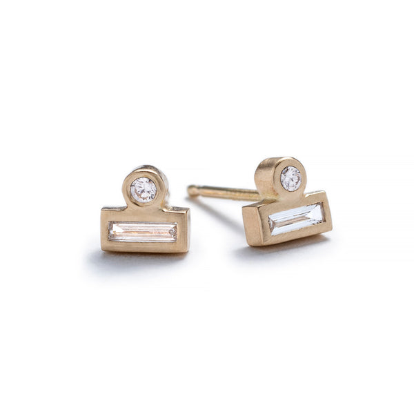 Tiny stud earrings of 14k yellow gold, featuring a small, round, white diamond set against the long side of a white diamond baguette. Hand-crafted in Portland, Oregon.