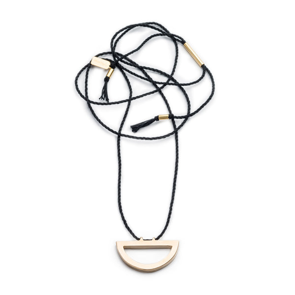 Modern, adjustable necklace of black Japanese cotton rope threaded along the long end of a cast bronze semi-circle pendant with brass tubing accents and black cotton fringe. Hand-crafted in Portland, Oregon.