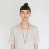 The betsy & iya black Japanese cotton rope and cast bronze semicircle Kanssa necklace, pictured on a model wearing a pale gray tunic.