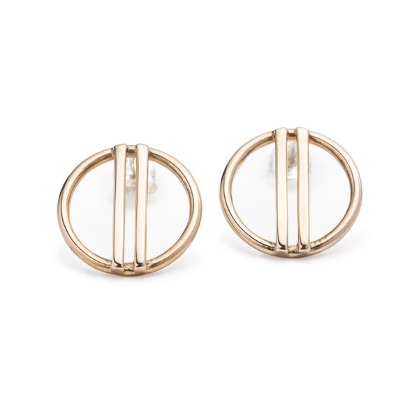 Minimal, modern, and shiny cast bronze stud earrings, featuring a small, open circle with two vertical bars running through the center. Hand-crafted in Portland, Oregon.