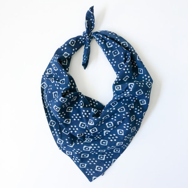 A blue and white patterned bandana, folded over and tied in a knot. Block printed by hand, the Billie Bandana from Maelu is designed in Portland, Oregon and handmade in India.