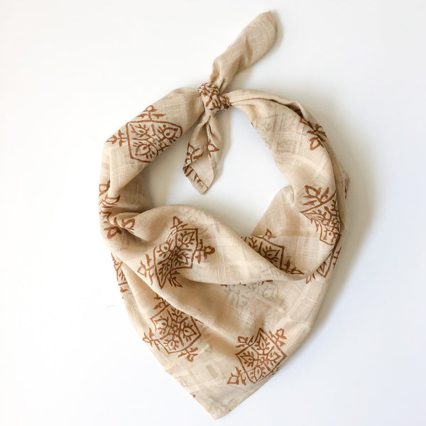 A golden brown and cream patterned bandana, folded over and tied in a knot. Block printed by hand, the Gold Compass Bandana from Maelu is designed in Portland, Oregon and handmade in India.