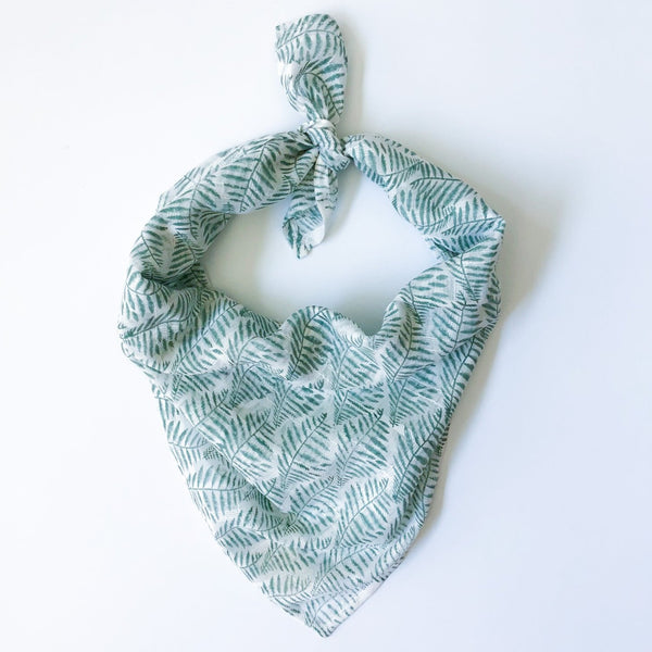 A green and white patterned bandana, folded over and tied in a knot. Block printed by hand, the Laguna Bandana from Maelu is designed in Portland, Oregon and handmade in India.