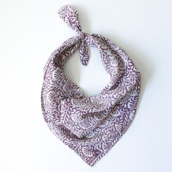 A purple and white patterned bandana, folded over and tied in a knot. Block printed by hand, the Lavender Bandana from Maelu is designed in Portland, Oregon and handmade in India.