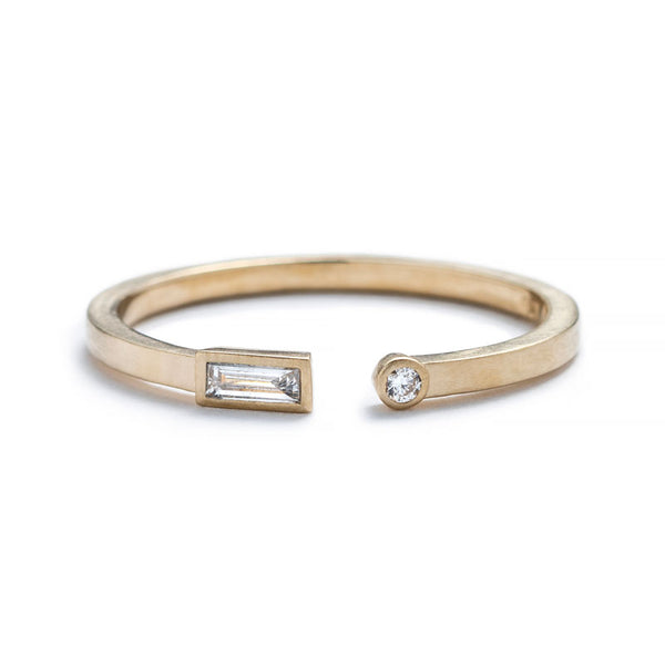 Thin, 14k yellow gold adjustable ring with a matte finish, bezel-set with a small, white diamond baguette on one end, and a small, white, round diamond on the opposite end. Hand-crafted in Portland, Oregon.