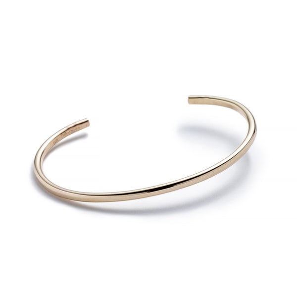 Minimalist, thin, and adjustable stacking cuff of 10k yellow gold hand-forged wire, with the betsy & iya logo engraved on the inside. Hand-crafted in Portland, Oregon.