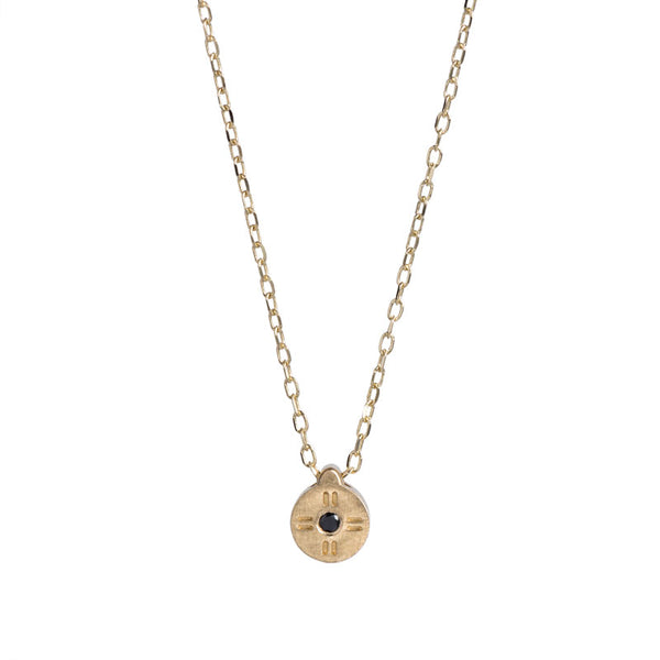 Tiny, circular pendant of 14k yellow gold, with subtle engraved details around a small black diamond, on a 14k gold chain. Hand-crafted in Portland, Oregon.
