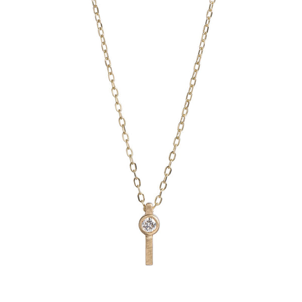Tiny, rectangular pendant of 14k yellow gold, topped with a round, bezel-set white diamond, and threaded with a delicate gold chain. Hand-crafted in Portland, Oregon.