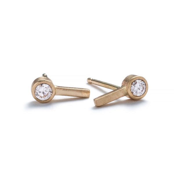 Tiny, ankh-shaped stud earrings of 14k yellow gold, topped with round, bezel-set white diamonds, and finished with 14k gold earring posts. Hand-crafted in Portland, Oregon.