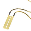 Long statement necklace featuring a vintage deco brass box chain, gray Japanese cotton accents, and a rectangular brass pendant with a thin, slit cutout down the center. Hand-crafted in Portland, Oregon.