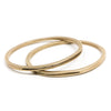 A pair of sturdy, circular, cast-bronze bangle bracelets, each with one long, slim, cutout slit in the metal. Hand-crafted in Portland, Oregon.