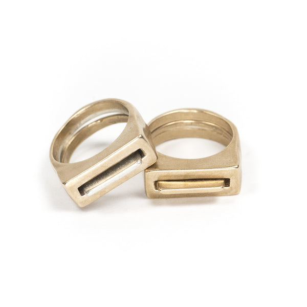A set of silver and cast bronze Tuyo and Mía rings, propped up against the edge of a set of all-bronze Tuyo and Mía rings. Hand-crafted in Portland, Oregon.