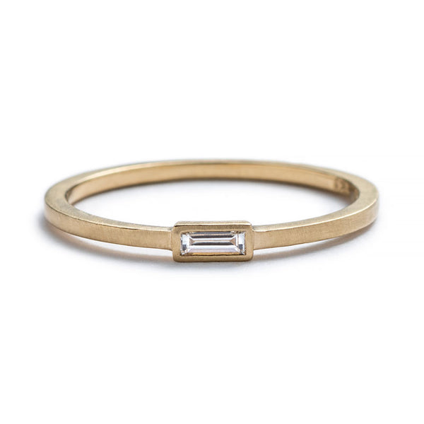 Thin, 14k yellow gold ring with a matte finish and a small, white diamond baguette bezel-set parallel to the band. Hand-crafted in Portland, Oregon.