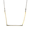 Three skinny golden brass bars form a geometric shape at the bottom of a long thin gunmetal chain.