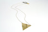 betsy & iya Sandstorm geometric necklace laying casually on a table.