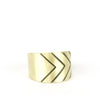 Gold brass band ring with simple black chevron lines on the edge.