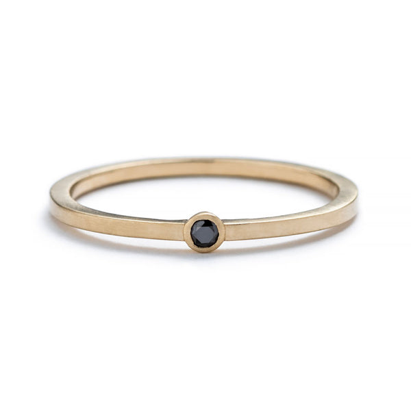 Thin, 14k yellow gold band with a matte finish, featuring a small, round, bezel-set black diamond. Hand-crafted in Portland, Oregon.