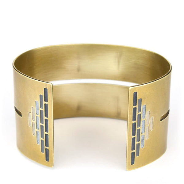 Wide, bold, brass cuff bracelet in the Portland colorway, with a cutout slit that runs through the center of the cuff and stops just short of a pyramid of grayscale paint on either end. Hand-crafted in Portland, Oregon.