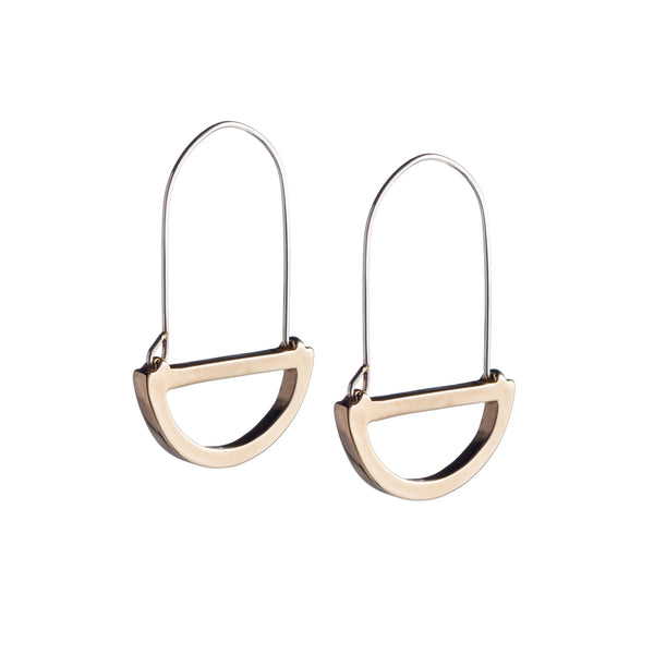 Modern, polished, cast bronze semicircle pendants hanging below long, hand-formed, sterling silver hoops. Hand-crafted in Portland, Oregon.