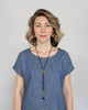 Betsy & iya's black Japanese cotton and brass Tassa bolo necklace, styled on a model with a cap-sleeve denim tunic and (now discontinued) brass betsy & iya Jo hoop earrings.