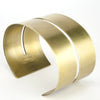 Wide, bold, brass cuff bracelet with a cutout that runs through the center of the cuff and stops just short of either end of the cuff, with the betsy & iya logo engraved on the inside. Hand-crafted in Portland, Oregon.