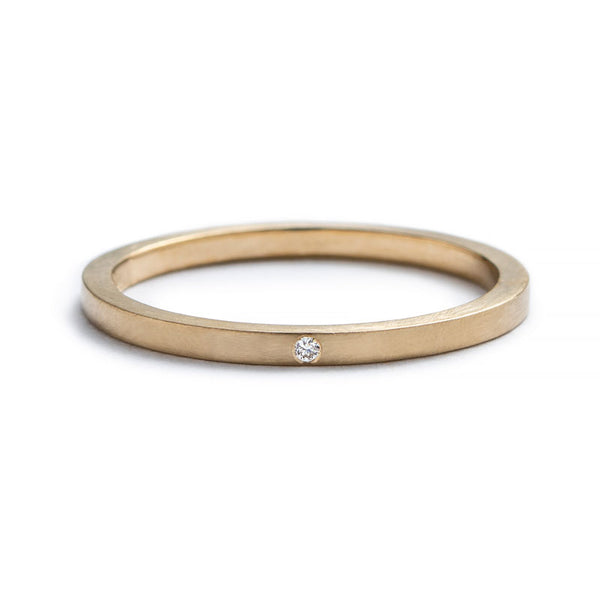 Thin, 14k yellow gold stacking band with a matte finish, and a tiny, round, flush-set white diamond. Hand-crafted in Portland, Oregon.