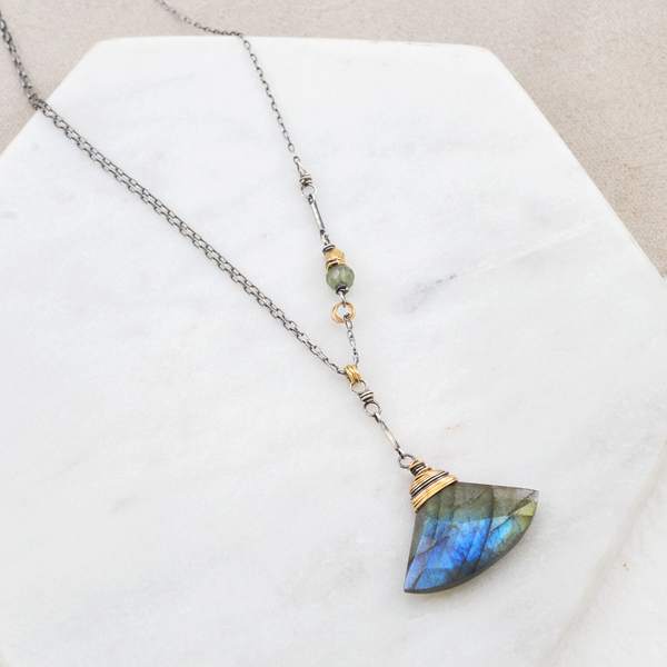 A labradorite necklace lays on a marble slab. The Luna Necklace features a green garnet bead and brass nugget on the sterling chain. Made in Portland, Oregon by designer Amy Olson.