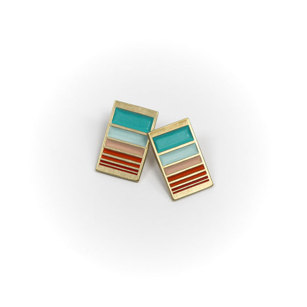 A pair of rectangular, cast-bronze stud earrings, decorated in our Mexico colorway, with a gradient of rich teal and red paint. Hand-crafted in Portland, Oregon.