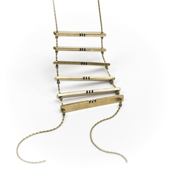 Six cast-bronze bars with black, painted notch details, strung together in the shape of a ladder with a long, clasp-less, brass chain. Hand-crafted in Portland, Oregon.