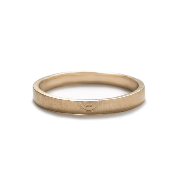 Thin, flat, 14k yellow gold band with a matte finish and a minimalistic, hand-carved, semi-circle design that is reminiscent of a rainbow. Hand-crafted in Portland, Oregon.