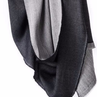 Merino wool scarf hangs in the air. One side is light grey and the other side is a dark charcoal grey or black. Black stitching can be seen on the edges. The Eden Reversible Scarf in Black is from Bloom & Give.