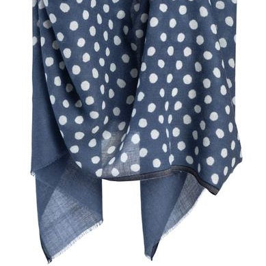 Blue scarf with white dots hangs in the air. The Maya Dot Scarf in Blue is from Bloom & Give.