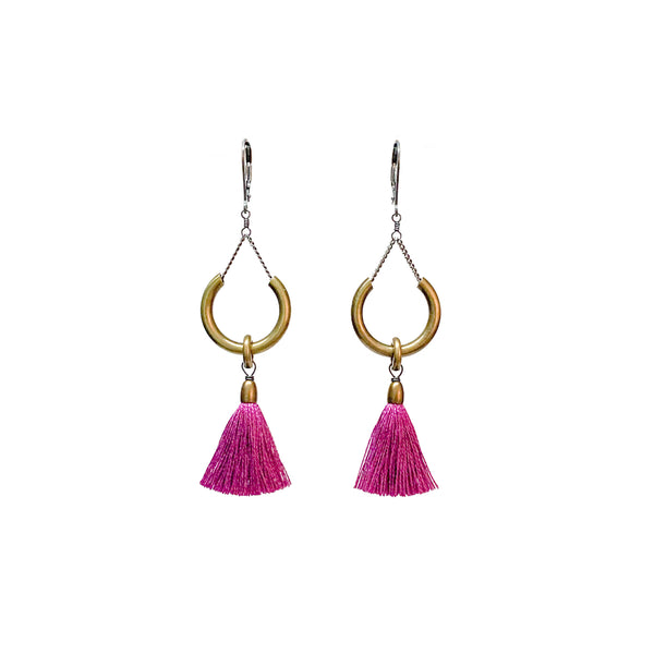 A pair of earrings with silver clasps, a brass ring and fuchsia tassels. The Duster Earrings in Hot Violet are from Portland designer Emily Bixler of BOET.