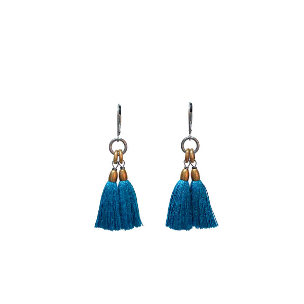 A pair of dangling earrings with teal tassels and brass rings topped with a silver leverback. The Fan Earrings in Peacock are from Portland designer Emily Bixler of BOET.