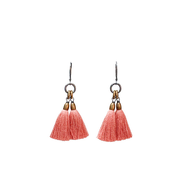 A pair of dangling earrings with blush pink tassels and brass rings topped with a silver leverback. The Fan Earrings in Shell are from Portland designer Emily Bixler of BOET.