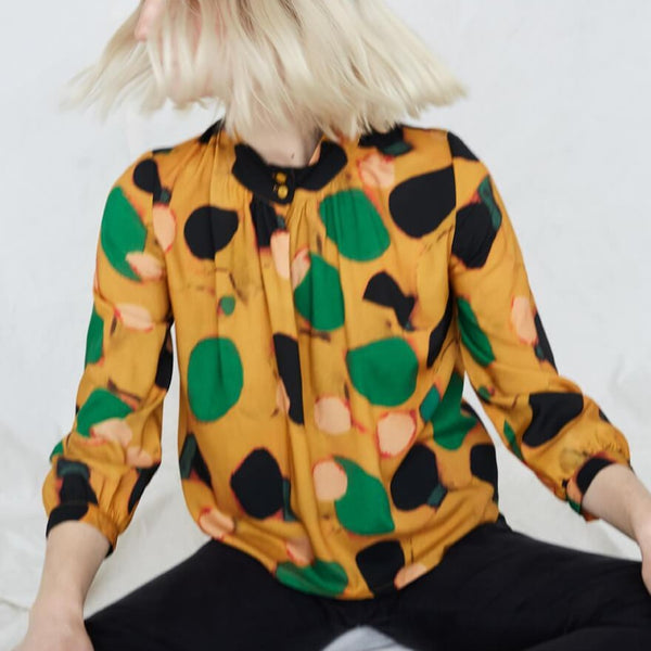 Blonde woman wears yellow blouse with green, pink and black dots. The woman is shaking her hair and sitting crossed-leg in black pants. The Acacia Top in Klimt is from Canadian designer Eve Gravel. Illustrative pattern is a collaboration with artist Catherine D'Amours.