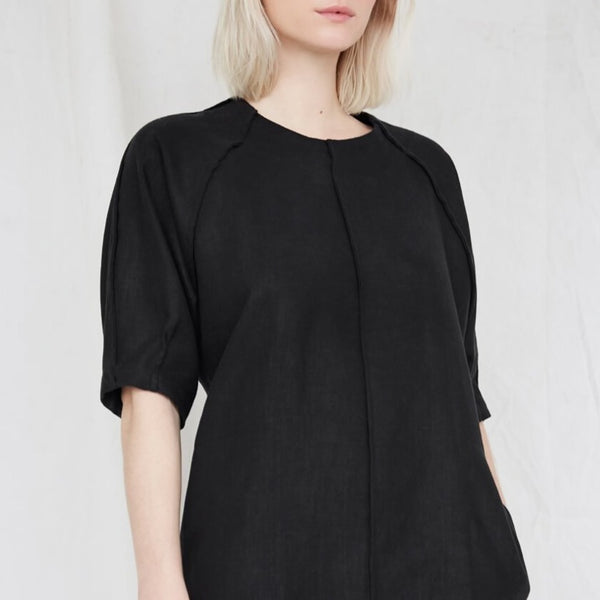 Blonde woman wears a slightly loose black dress with raglan sleeves. The Moonless Night Dress in Black features a sleek stitching detail down the front. The dress is from Canadian designer Eve Gravel.