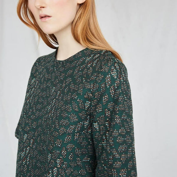 Red-haired woman wears an emerald top with intricate jacquard detailing. The Night Bird top is from Canadian designer Eve Gravel.