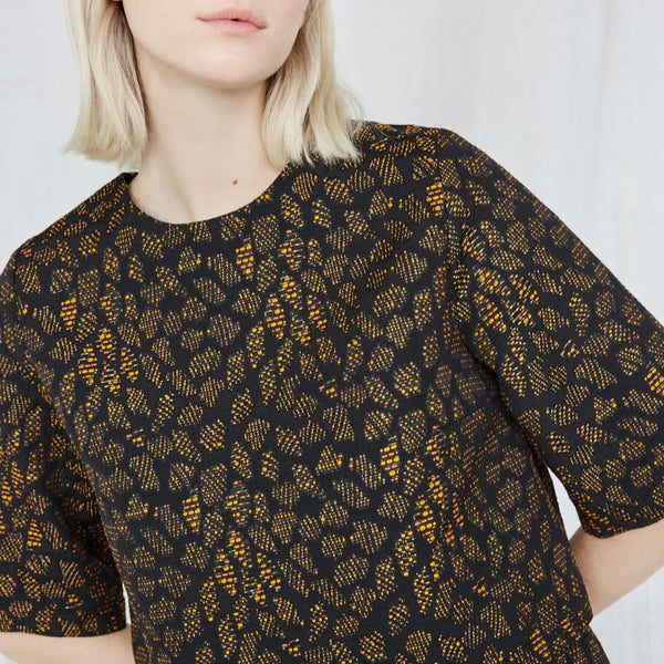 Blonde woman wears an orange and black top with intricate jacquard detailing. The Night Bird top is from Canadian designer Eve Gravel.