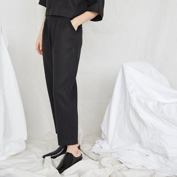 Model is standing with one hand in a pocket and wears a black top and matching pants. The Terre Sauvage Pants in black have pleats in the front and belt loops. The pants fall above the model's ankle and she is wearing black loafers. The pants are from Canadian designer Eve Gravel.