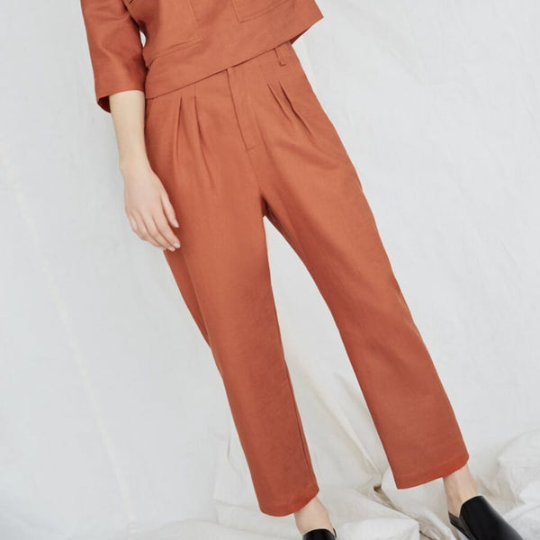 Model is standing at an angle and wears an orange top and matching pants. The Terre Sauvage Pants in burnt orange have pleats in the front and belt loops. The pants fall above the model's ankle and she is wearing black loafers. The pants are from Canadian designer Eve Gravel.