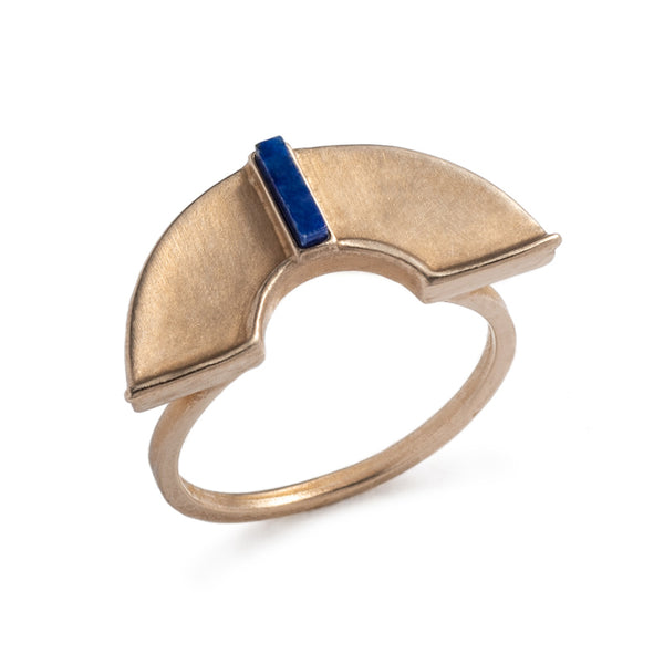 A unique, cast-bronze, half-circle shield, set atop a bronze band, and inlaid with a rectangular, blue, lapis lazuli stone. Hand-crafted in Portland, Oregon.