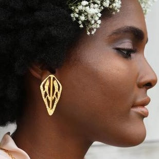 Woman in a profile view wears brass earrings and white flowers in her hair. The Alien Key Post earrings are from designer Lingua Nigra.