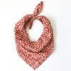 A red and cream patterned bandana, folded over and tied in a knot. Block printed by hand, the Fez Bandana from Maelu is designed in Portland, Oregon and handmade in India.